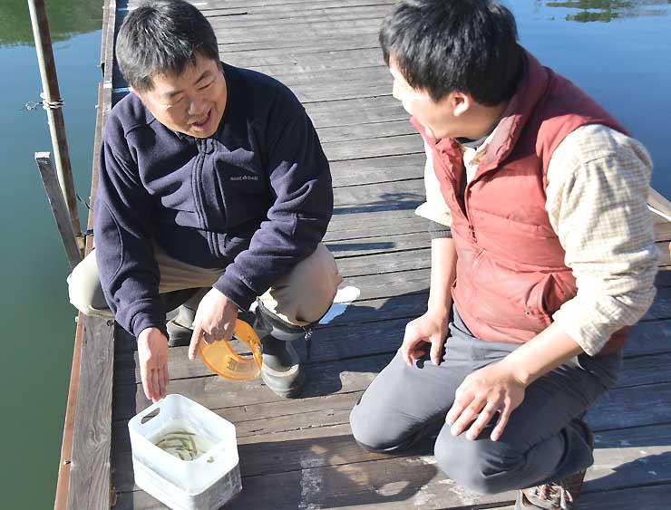 試し釣りで捕ったワカサギを確認する小沢さん(右)と宮田さん=7日午後2時半、美鈴湖