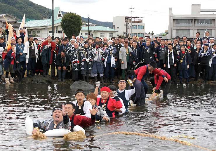 初島神社の御柱祭で、若者を乗せボートに引かれて諏訪湖に入る御柱。諏訪地方観光連盟はこうした小宮の御柱祭での観光客受け入れを目指す=2010年10月