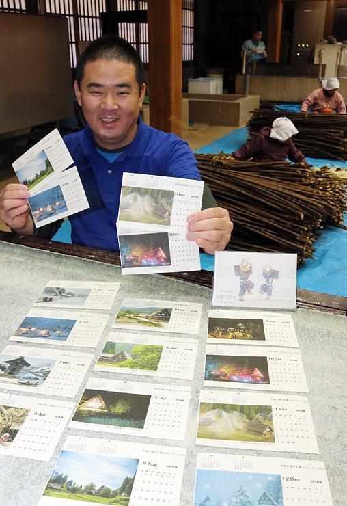 和紙原料コウゾの皮はぎ作業が進む作業場で、和紙カレンダーを手にするアマ写真家の奈雲さん
