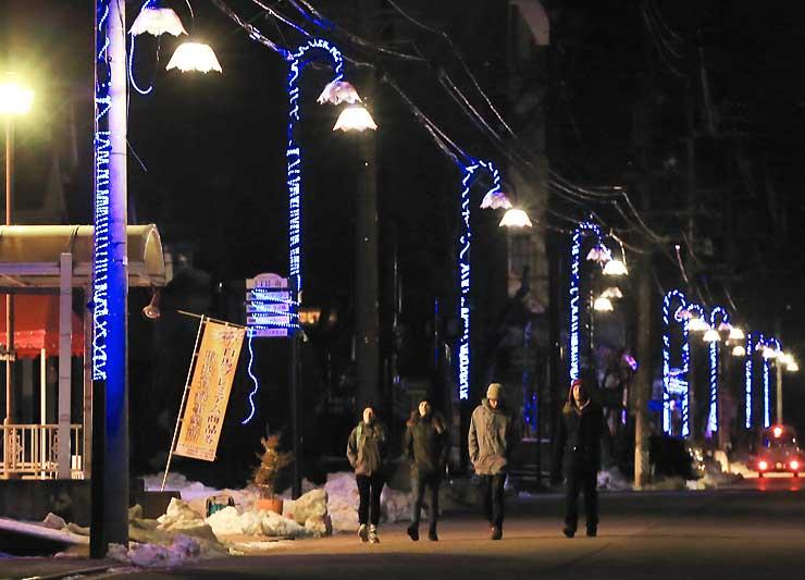 スキーシーズンを迎え、村内を歩く外国人観光客の姿が増えてきた白馬村=9日夜、白馬村北城のエコーランド地区