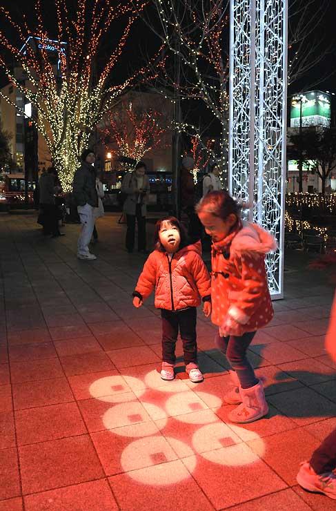 地面に赤く照らし出された六文銭や周辺の木々を彩るイルミネーションに、子どもも大喜び=9日午後6時36分、上田市の上田駅前お城口広場
