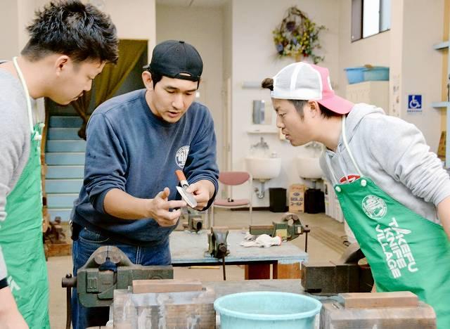 タケフナイフビレッジの職人(中央)から研ぎのポイントなどについて教わる北村さんとその知人
