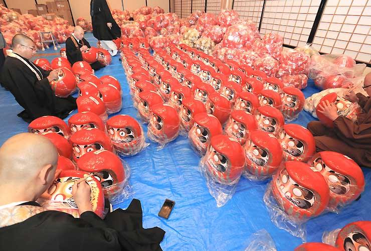 だるまの左目に梵字を書き入れる僧侶たち=11日、長野市の善光寺大勧進