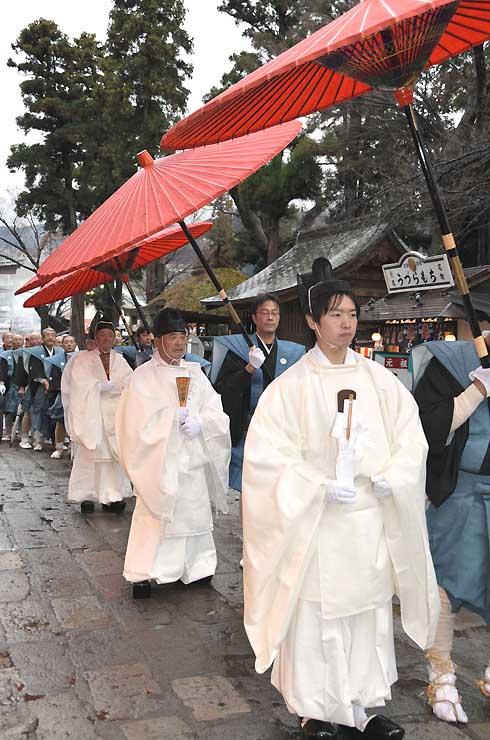 白装束で武水別神社に向かって歩く頭人ら
