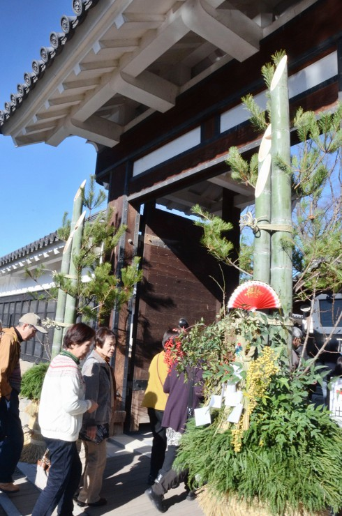 松本城の黒門に設置された門松飾りに目をやる観光客