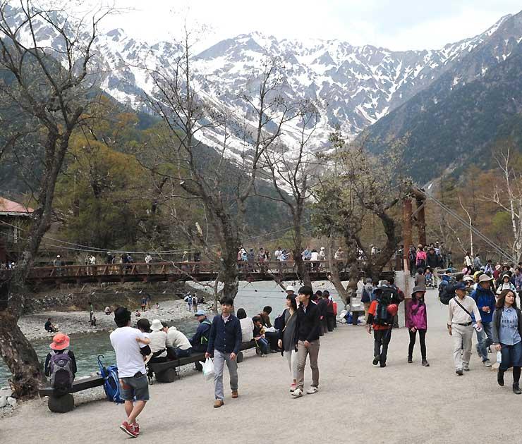 河童橋付近を散策する観光客ら。上高地の今年の開山期間中の入り込みは微減となった=5月