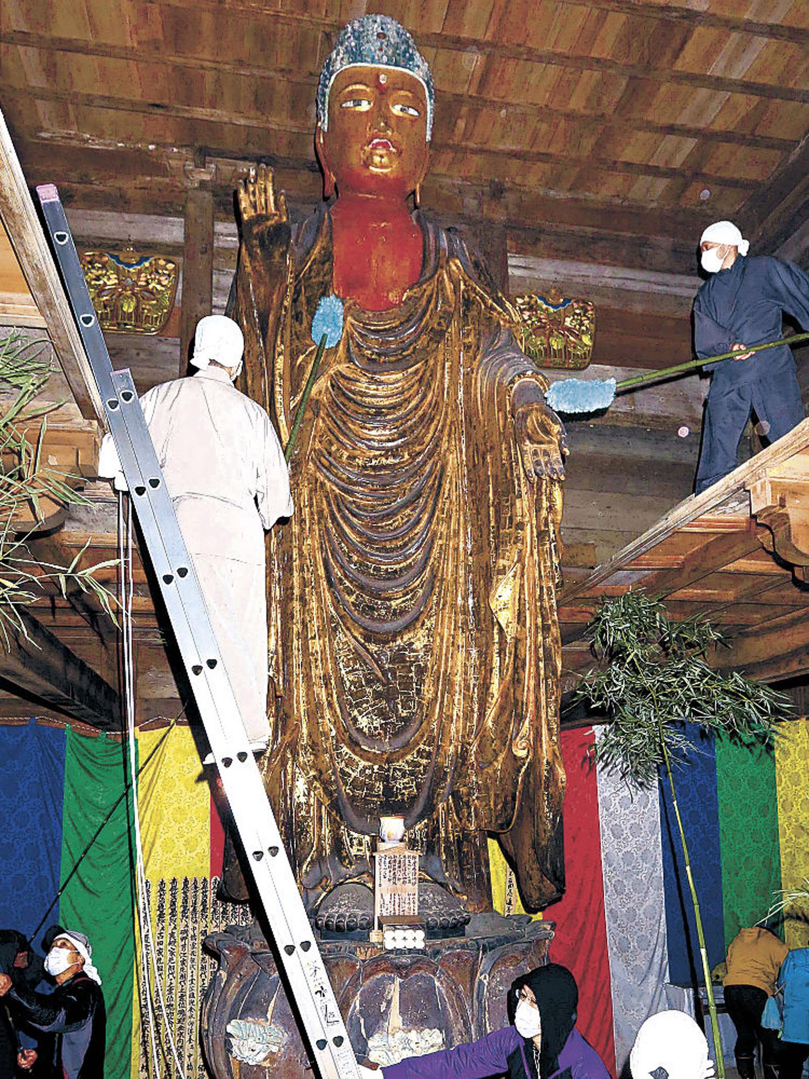 仏像にたまったほこりを払い落とす僧侶や檀信徒=15日午前10時35分、羽咋市滝谷町の妙成寺