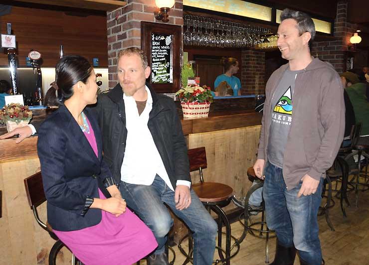 開店したレストランバーで談笑するコウバーンさん(右)とベイコンさん夫婦=15日午後5時半、白馬村