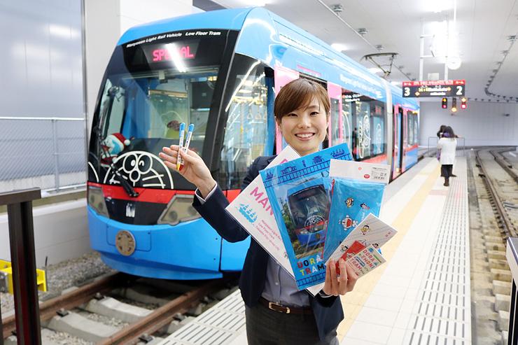 「トラムでGO!シリーズ」の新商品を紹介する松田さん=万葉線高岡駅