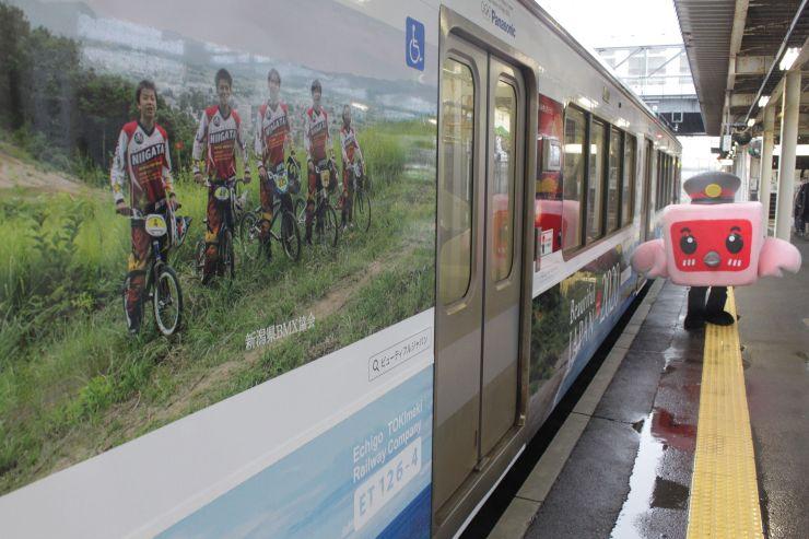BMXの選手や県内の風景の写真で覆われたラッピング列車=上越市の直江津駅