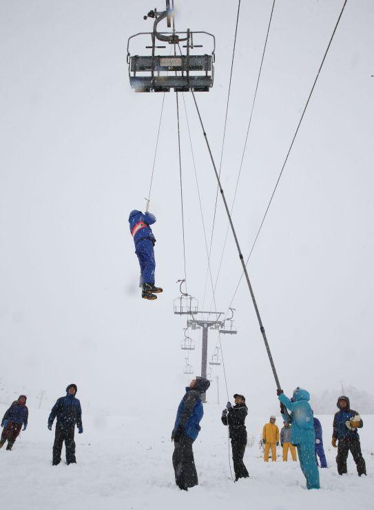 雪が降りしきる中、リフトからスキー客を下ろす訓練をする参加者=17日、上越市安塚区須川
