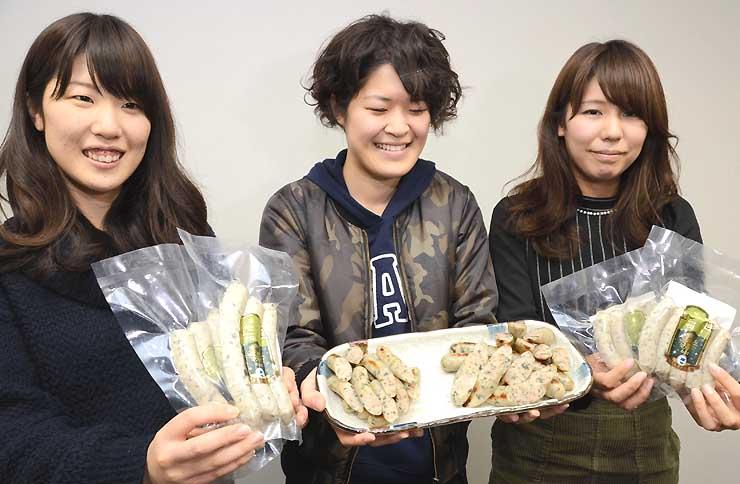 安曇野市産ワサビの葉が入ったソーセージを手にする松本大の学生=21日、松本市の松本大