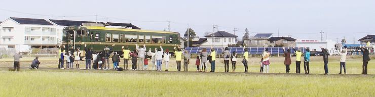 城端線沿線に集まり、べるもんたに手を振る南砺市田中の住民たち