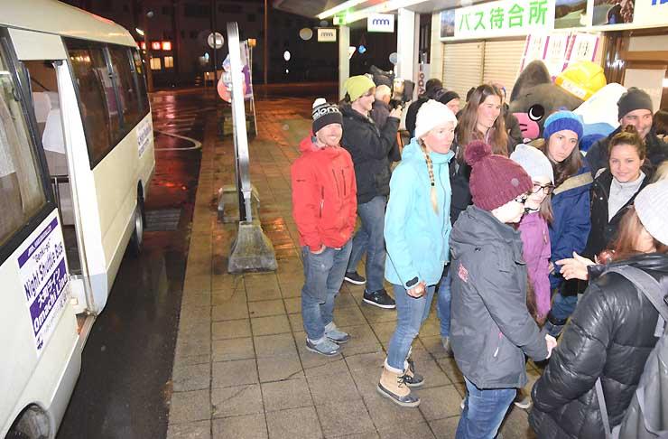 白馬村から夜間シャトルバスで大町市のJR信濃大町駅前に到着した外国人たち=23日夜