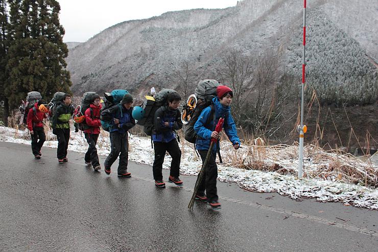 荷物を背負って歩く九州大山岳部員ら=上市町伊折
