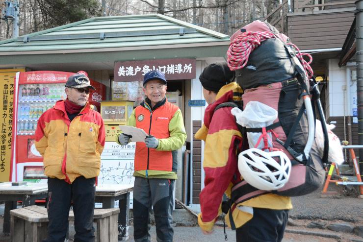 美濃戸口で登山者(右)から入山届を受け取って内容を確認し、「行ってらっしゃい」と見送る遭対協の救助隊員