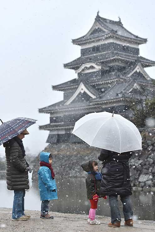 雪が舞う中を散歩する家族連れ=27日午前8時50分、松本城公園