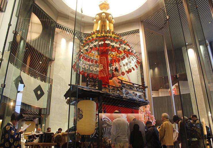 豪華な装飾が施された守山町の山車を囲み、神事に参加する同町の住民ら=高岡御車山会館