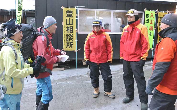 登山相談所で雪などの情報を聞く入山者(左の2人)=松本市安曇の中の湯