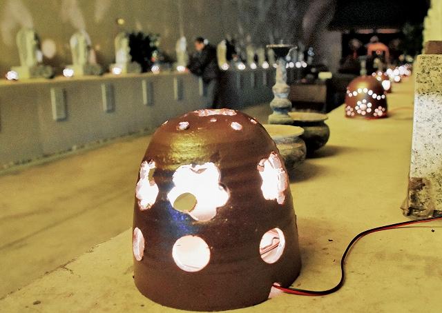 正月を前に設置された越前焼の明かりとり。石仏を優しく照らす=30日、福井県越前町の玉川洞窟観音