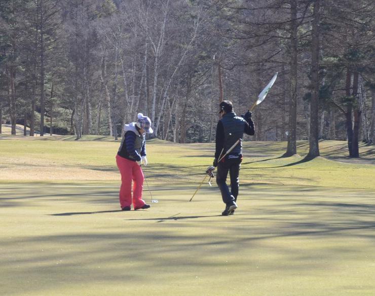 雪のないゴルフ場で年末にプレーを楽しむ人たち