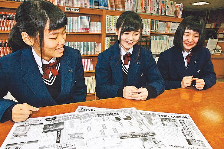 アウトレット特集を組んだ「学窓新聞」を前に「小矢部の活性化に貢献したい」と話す左から毎田部長、加藤さん、山田さん