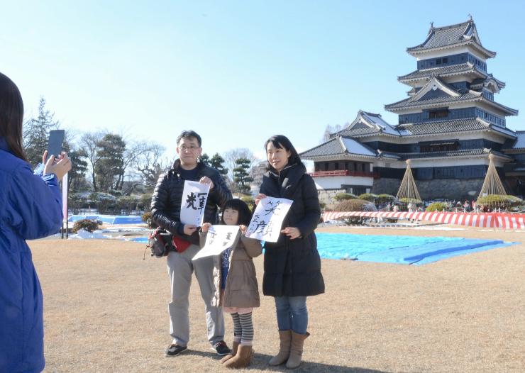 書き初めをした紙を持って松本城天守と写真に納まる親子