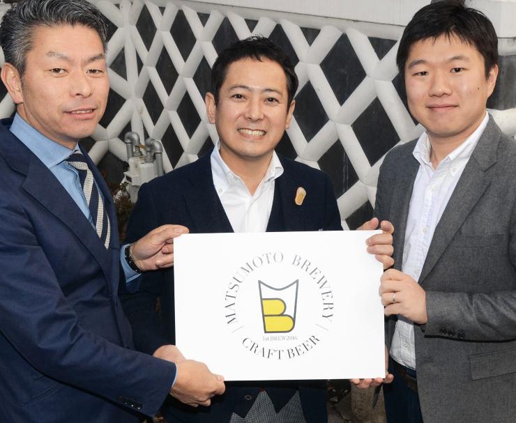 新会社のロゴマークを手にする林さん(中央)ら=松本市