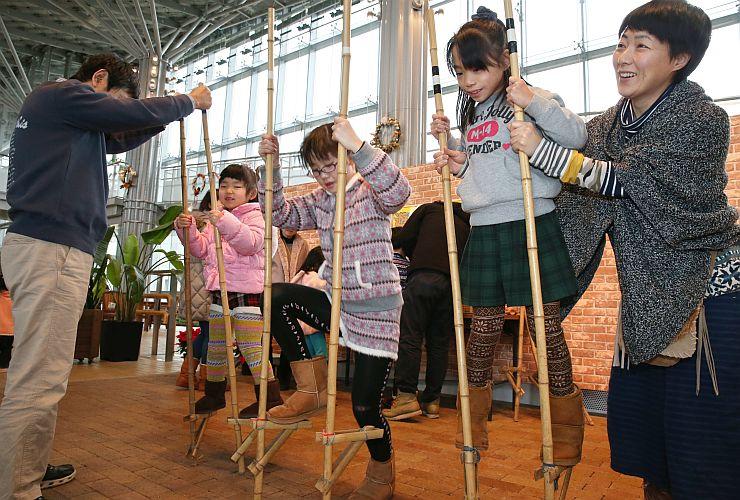 竹馬で遊ぶ子どもたち=3日、長岡市の国営越後丘陵公園