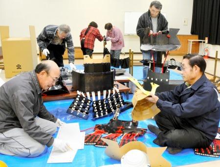 段ボールなどで甲冑作りに取り組む奉賛会メンバー=昨年12月17日夜、福井県あわら市柿原のさくらセンター