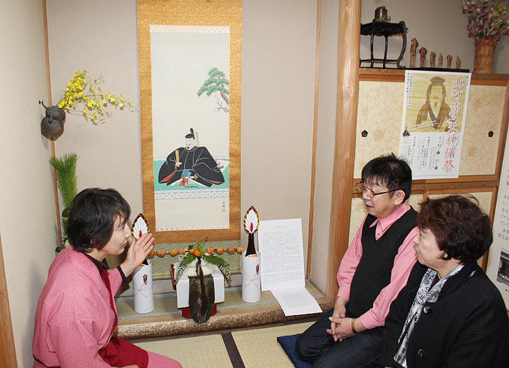来店客に高岡と天神信仰との関係について説明する沢田さん(左)=大仏茶屋