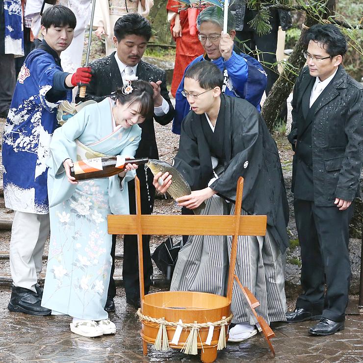 コイにお神酒を飲ませる厄年の男女=庄川水記念公園