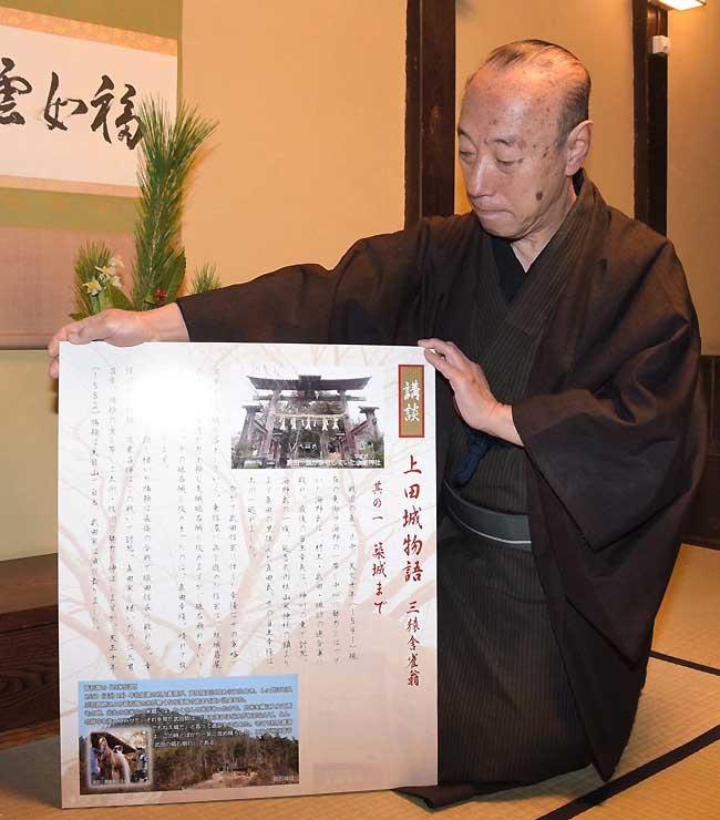 「講談・上田城物語」のパネルの試作品を手にする益子さん=8日、上田市