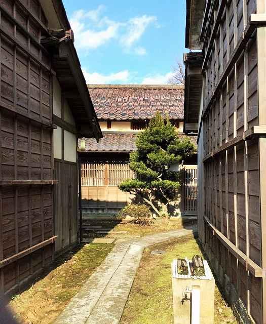 二つの蔵の間から見える小松長生さんの生家(奥)。改修して4月にレストランがオープンする=福井県坂井市三国町崎