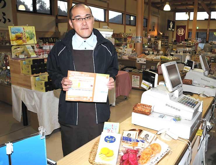 人気投票の品が置かれ、スタンプラリーをPRする「道の駅木曽福島」の従業員