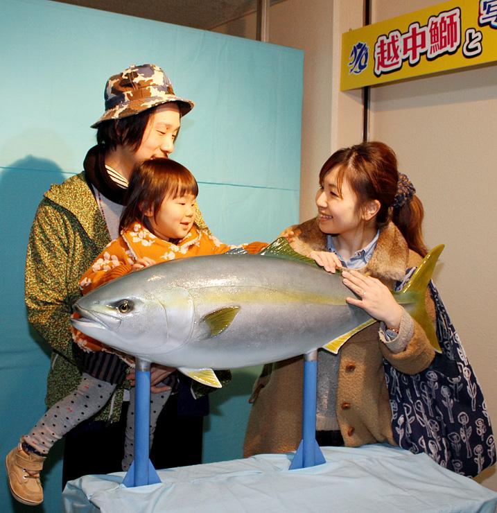 ブリの模型と記念撮影をする来館者=魚津水族館