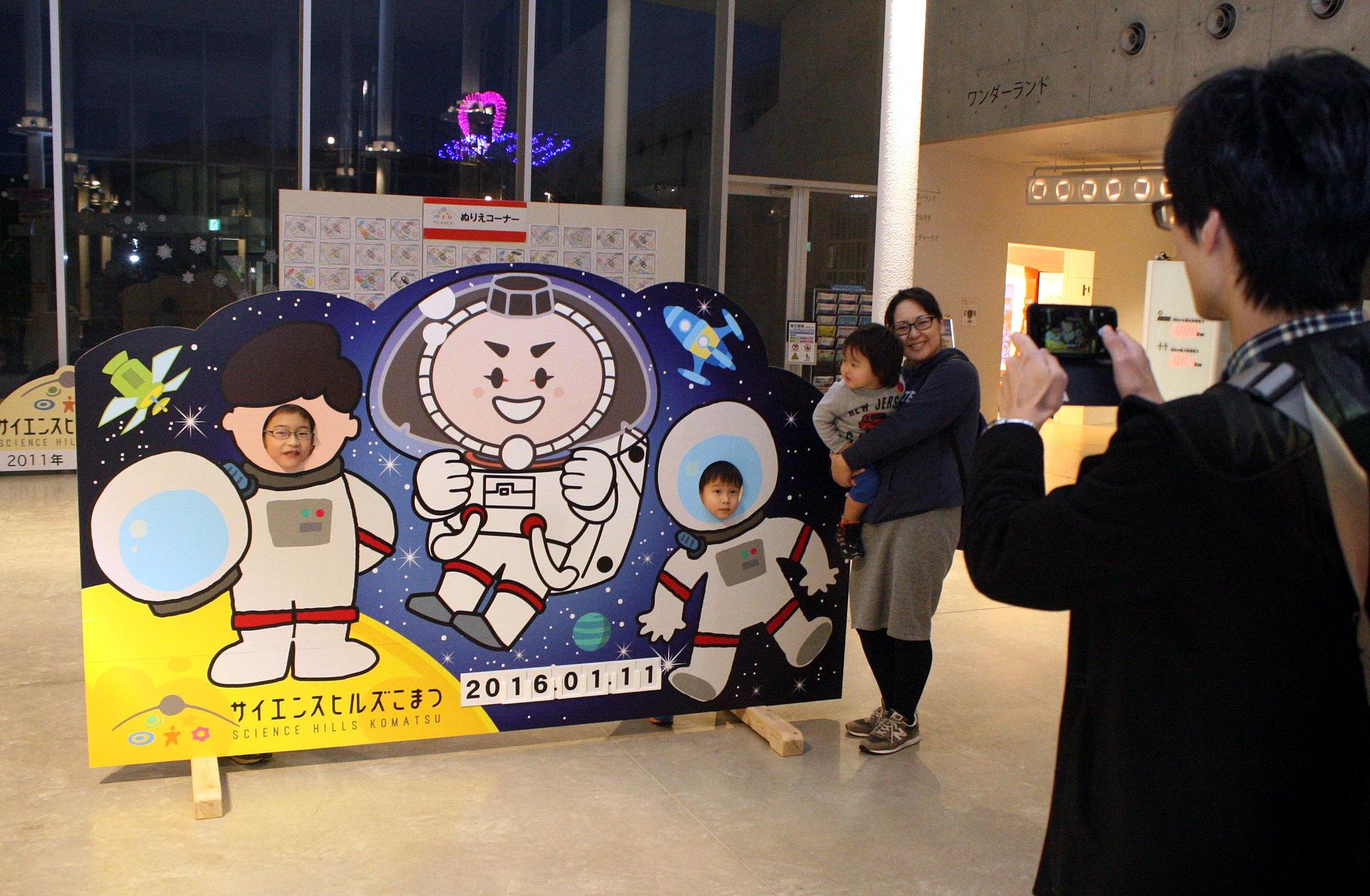 宇宙飛行士姿のカブッキーとともに記念撮影を楽しむ家族連れ=小松市のサイエンスヒルズこまつ