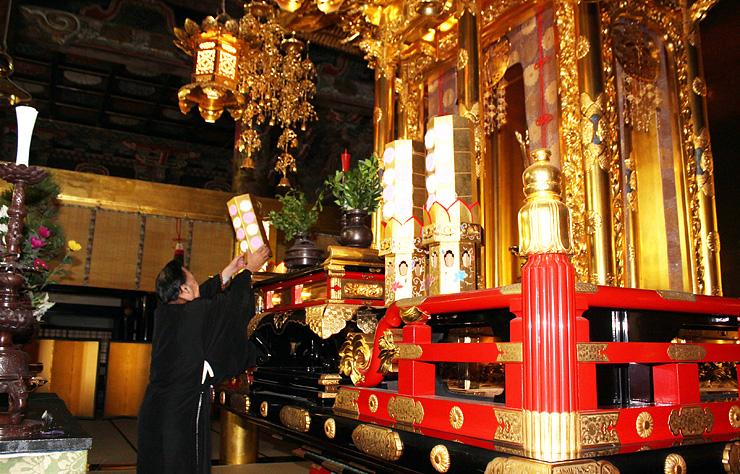 宮殿に飾り付けを行う土山住職(左)=勝興寺