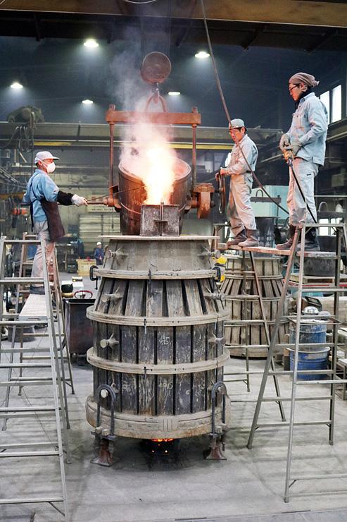 鋳型に溶けた合金を流し込む職人=老子製作所