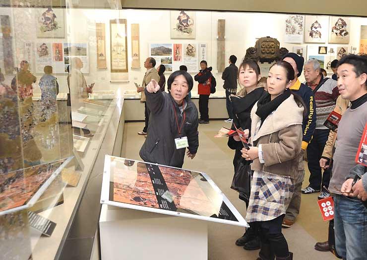 真田氏歴史館で、観光客に真田氏関連の史料を指さし解説する西牧会長