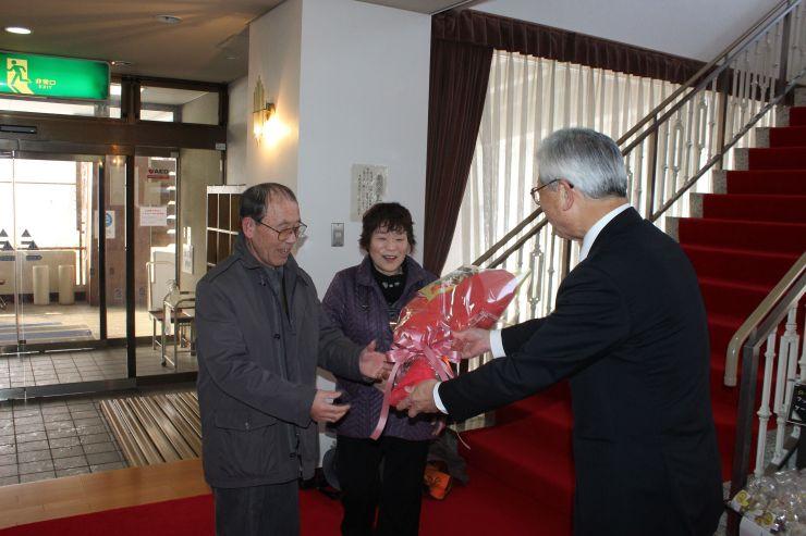 市川達孝副市長から花束を受け取る木賀公平さん、政子さん夫婦=13日、妙高市関川