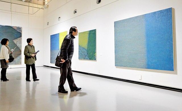 開幕と同時に会場に訪れ、熱心に作品を見る来場者=16日、福井県あわら市の金津創作の森