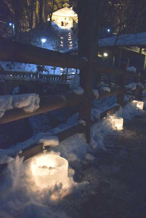 道の両脇で光る「氷灯ろう夢祈願」の灯籠。後方はライトアップされた薬師堂