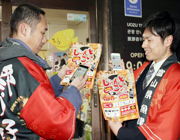 チラシを手にアプリの使い方を紹介する魚津市職員