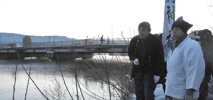 今冬初めて広く氷が張った諏訪湖を見つめる宮坂宮司(右)=21日午前7時前、諏訪市豊田の舟渡橋付近