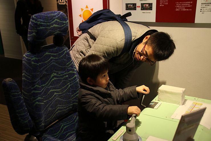 リニューアルを機に導入した運転シミュレーターを楽しむ親子=新潟市秋葉区の新津鉄道資料館