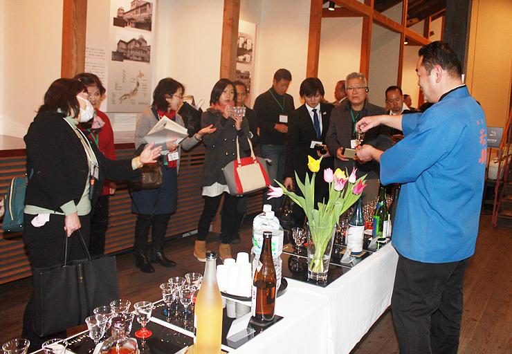 若鶴酒造の大正蔵で日本酒について説明を受けるタイとシンガポールの観光関係者