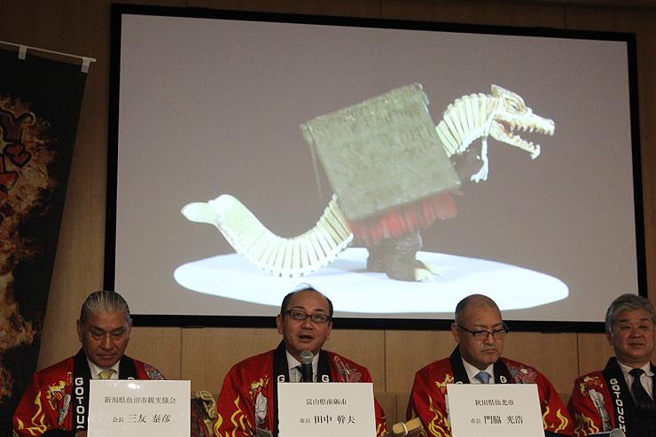 スクリーンに映されたご当地怪獣「デデレコデン」を紹介する田中南砺市長(左から2人目)=講談社本社