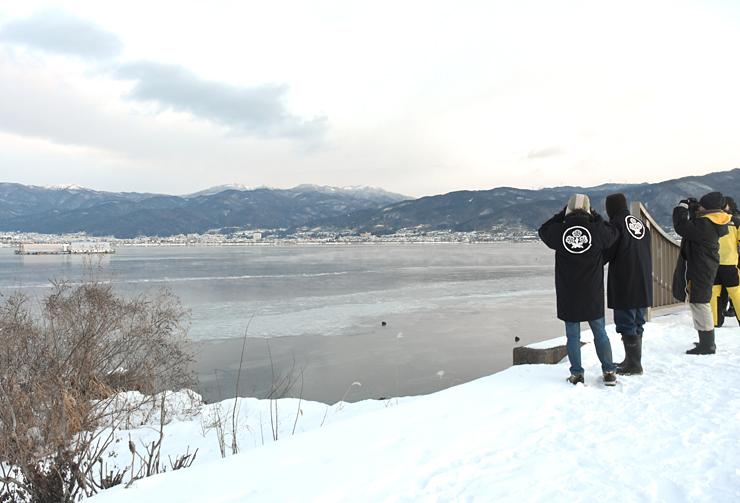 沖合まで凍った湖面を眺め、御神渡り出現に期待を寄せる八剣神社の宮司や氏子ら=25日、諏訪市豊田