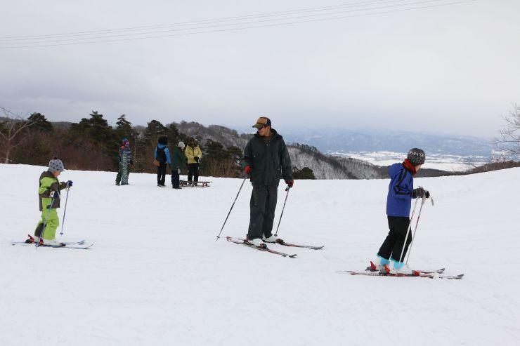 市営平スキー場での今季初滑りを楽しむ家族連れら=23日、佐渡市金井新保